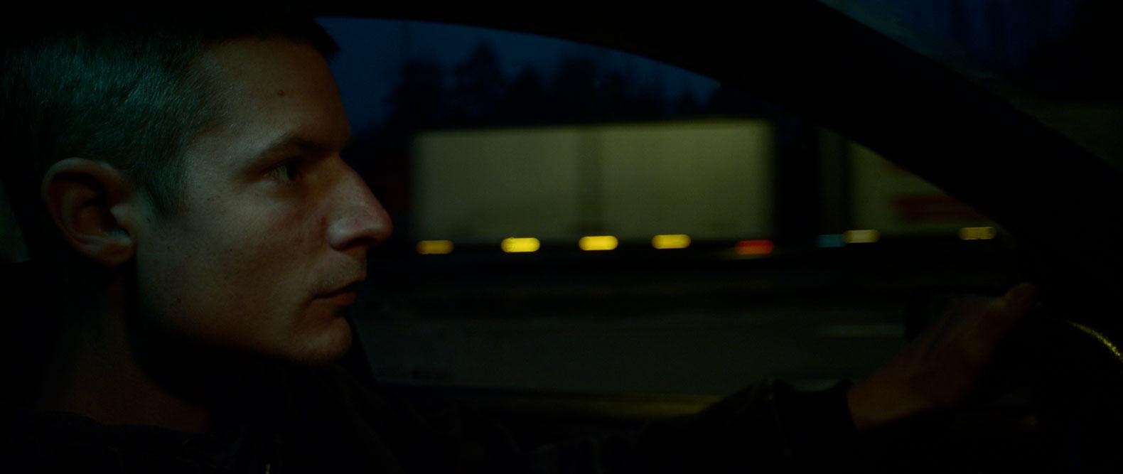 Sivusta kuvattu mies ajaa autolla